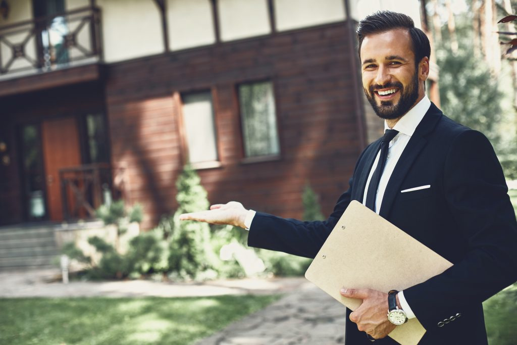 Cheerful professional young realtor looking happy and smiling while demonstrating the house
